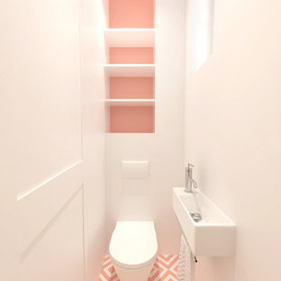 他の地域の小さいモダンスタイルのおしゃれなトイレ・洗面所 (壁掛け式トイレ、白い壁、セメントタイルの床、壁付け型シンク、マルチカラーの床) の写真