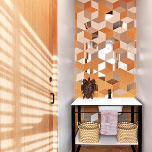 ニューヨークのエクレクティックスタイルのおしゃれなトイレ・洗面所 (オレンジのタイル、黄色い壁、オレンジの床、アンダーカウンター洗面器、白い洗面カウンター) の写真