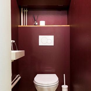 На фото: со средним бюджетом маленькие туалеты в современном стиле с инсталляцией, красными стенами, полом из цементной плитки и подвесной раковиной