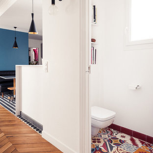 Photo of a medium sized retro cloakroom in Paris with a wall mounted toilet, multi-coloured tiles, white walls and ceramic flooring.