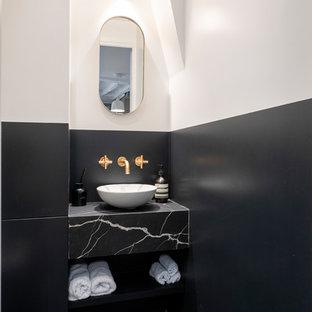 Aménagement d'un WC et toilettes contemporain avec un placard sans porte, des portes de placard noires, un mur multicolore, une vasque, un sol noir et un plan de toilette noir.