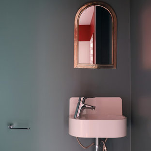 Cette photo montre un petit WC et toilettes tendance avec un placard à porte plane, des portes de placard grises, un WC suspendu, un carrelage blanc, du carrelage en marbre, un mur vert, un sol en linoléum, un lavabo suspendu et un sol gris.