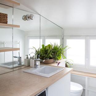 Aménagement d'un WC et toilettes scandinave avec un mur blanc, un lavabo posé, un sol blanc et un plan de toilette beige.