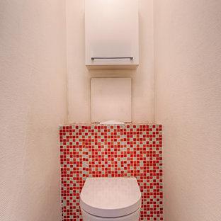 Стильный дизайн: туалет в современном стиле с красными фасадами, инсталляцией, белой плиткой, керамической плиткой, белыми стенами, полом из керамической плитки, подвесной раковиной, столешницей из ламината и бежевым полом - последний тренд