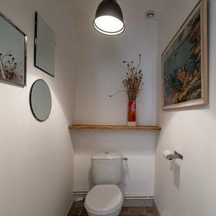 Cette photo montre un petit WC et toilettes nature avec un WC à poser, un mur blanc, un sol en carreaux de ciment et un sol beige.