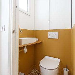 パリの小さいおしゃれなトイレ・洗面所 (インセット扉のキャビネット、白いキャビネット、壁掛け式トイレ、黄色い壁、セメントタイルの床、ベッセル式洗面器、木製洗面台、黄色い床、ベージュのカウンター、造り付け洗面台) の写真