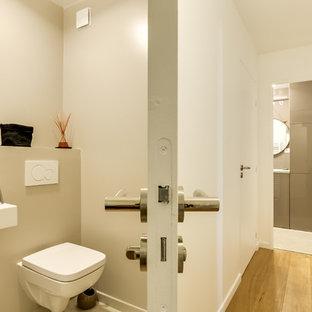 Идея дизайна: туалет среднего размера в современном стиле с фасадами с декоративным кантом, зелеными фасадами, инсталляцией, бежевыми стенами, полом из керамической плитки, подвесной раковиной и бежевым полом