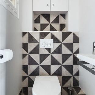 Esempio di un piccolo bagno di servizio minimal con ante lisce, ante bianche, WC sospeso, pistrelle in bianco e nero, piastrelle di cemento, pareti bianche, pavimento in cementine, lavabo sospeso e pavimento nero