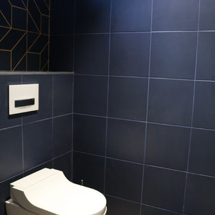 Modelo de aseo actual, de tamaño medio, con sanitario de pared, baldosas y/o azulejos azules, baldosas y/o azulejos de cerámica, parades naranjas, suelo de madera clara, encimera de azulejos, suelo marrón y encimeras azules