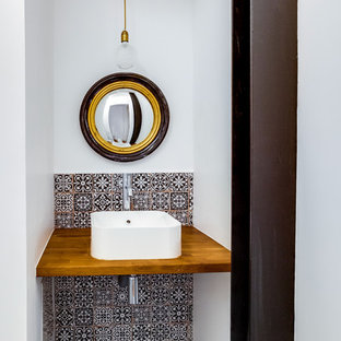 Design ideas for a small contemporary cloakroom in Paris with a wall mounted toilet, multi-coloured tiles, cement tiles, white walls, cement flooring, a console sink and multi-coloured floors.