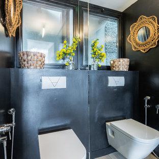 Cette image montre un WC et toilettes bohème avec un WC suspendu, un mur noir, un sol en bois clair et un sol beige.