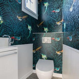 Exemple d'un petit WC et toilettes chic avec un placard à porte affleurante, un WC suspendu, un carrelage blanc, un mur multicolore, sol en terrazzo, un lavabo suspendu, un sol gris, des portes de placard blanches et un plan de toilette blanc.