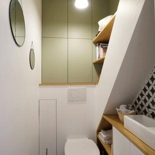 Cette photo montre un petit WC et toilettes tendance avec un placard à porte plane, des portes de placard blanches, un WC suspendu, un carrelage noir et blanc, un mur blanc, une vasque, un plan de toilette en bois, un sol noir, un plan de toilette beige et meuble-lavabo suspendu.