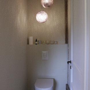 Imagen de aseo campestre, pequeño, con sanitario de pared, paredes beige y suelo de baldosas de terracota