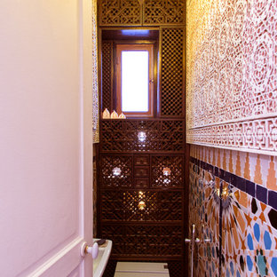 This is an example of a small mediterranean cloakroom in Paris with brown cabinets, a one-piece toilet, multi-coloured tiles, terracotta tiles, multi-coloured walls and a wall-mounted sink.