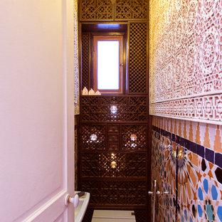 パリの小さい地中海スタイルのおしゃれなトイレ・洗面所 (茶色いキャビネット、一体型トイレ、マルチカラーのタイル、テラコッタタイル、マルチカラーの壁、壁付け型シンク) の写真