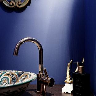 他の地域の小さいカントリー風おしゃれなトイレ・洗面所 (シェーカースタイル扉のキャビネット、茶色いキャビネット、壁掛け式トイレ、青いタイル、セメントタイル、青い壁、竹フローリング、オーバーカウンターシンク、木製洗面台、茶色い床、ブラウンの洗面カウンター) の写真