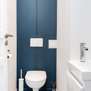 Imagen de aseo minimalista, pequeño, con armarios con rebordes decorativos, puertas de armario azules, sanitario de pared, baldosas y/o azulejos blancos, paredes azules, suelo de azulejos de cemento, lavabo suspendido, encimera de acrílico, suelo gris y encimeras blancas