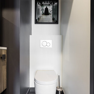Design ideas for a small contemporary cloakroom in Paris with a wall mounted toilet, slate flooring and a wall-mounted sink.