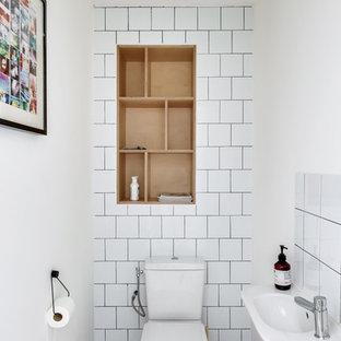 Cette photo montre un WC et toilettes tendance avec un placard sans porte, un WC séparé, un carrelage blanc, des carreaux de porcelaine, un mur blanc, un plan vasque et un sol gris.