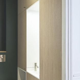 Ejemplo de aseo actual con sanitario de pared, paredes verdes, suelo de baldosas de cerámica, lavabo integrado, encimera de acrílico y suelo gris
