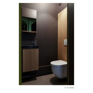 Пример оригинального дизайна: туалет среднего размера в современном стиле с фасадами с филенкой типа жалюзи, светлыми деревянными фасадами, инсталляцией, коричневыми стенами, полом из керамической плитки, консольной раковиной, мраморной столешницей, коричневым полом и серой столешницей
