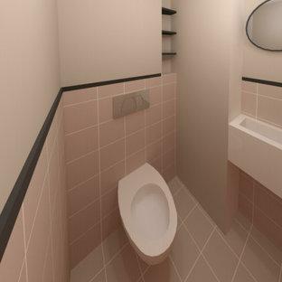 Cette photo montre un WC et toilettes tendance de taille moyenne avec des portes de placard beiges, un WC suspendu, un mur rose, un lavabo suspendu et un sol rose.