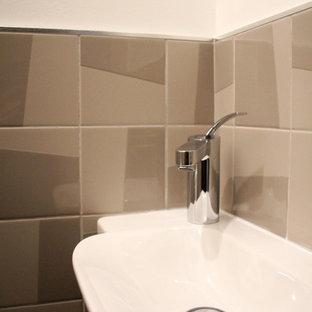 На фото: туалет среднего размера в стиле модернизм с раздельным унитазом, коричневой плиткой, терракотовой плиткой, бежевыми стенами, полом из ламината, столешницей из плитки и бежевым полом