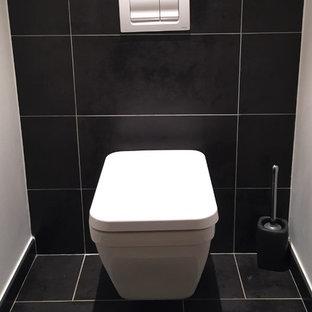 Esempio di un piccolo bagno di servizio contemporaneo con WC sospeso, piastrelle nere, pistrelle in bianco e nero, pareti nere, pavimento in cementine e pavimento nero