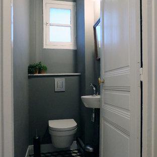パリの小さいコンテンポラリースタイルのおしゃれなトイレ・洗面所 (壁掛け式トイレ、グレーの壁、壁付け型シンク、セメントタイルの床、マルチカラーのタイル) の写真