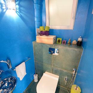 Cette image montre un WC et toilettes ethnique avec des portes de placard en bois clair, un WC suspendu, un carrelage vert, des carreaux de céramique, un mur bleu, un sol en carrelage de céramique et un lavabo suspendu.