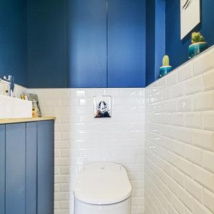 パリのコンテンポラリースタイルのおしゃれなトイレ・洗面所 (インセット扉のキャビネット、青いキャビネット、壁掛け式トイレ、白いタイル、サブウェイタイル、青い壁、セメントタイルの床、ベッセル式洗面器、木製洗面台、青い床、オレンジの洗面カウンター) の写真