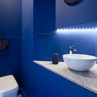 パリのコンテンポラリースタイルのおしゃれなトイレ・洗面所 (フラットパネル扉のキャビネット、青いキャビネット、壁掛け式トイレ、青い壁、ベッセル式洗面器、青い床、グレーの洗面カウンター) の写真