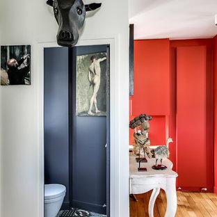 Свежая идея для дизайна: маленький туалет в современном стиле с плоскими фасадами, красными фасадами, инсталляцией, черными стенами, полом из керамической плитки и разноцветным полом - отличное фото интерьера