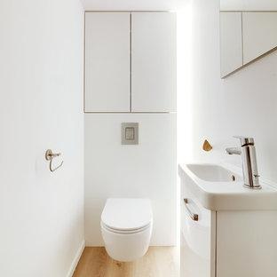 Идея дизайна: маленький туалет в стиле модернизм с фасадами с декоративным кантом, белыми фасадами, инсталляцией, белыми стенами, полом из ламината и подвесной раковиной
