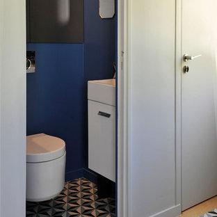 Ejemplo de aseo actual, pequeño, con armarios con rebordes decorativos, puertas de armario blancas, sanitario de pared, paredes azules, suelo vinílico, lavabo suspendido, suelo azul y encimeras blancas