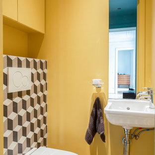 Aménagement d'un WC et toilettes contemporain avec un WC suspendu, un carrelage multicolore, un mur jaune et un lavabo suspendu.