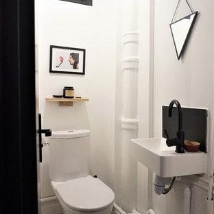 Idée de décoration pour un petit WC et toilettes design avec un mur blanc, un lavabo suspendu et un sol multicolore.