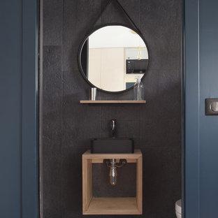 Cette image montre un petit WC et toilettes design avec un placard sans porte, des portes de placard en bois clair, un carrelage noir, un mur noir, une vasque, un plan de toilette en bois, un sol marron, un WC suspendu, des carreaux de béton et un sol en carreau de terre cuite.