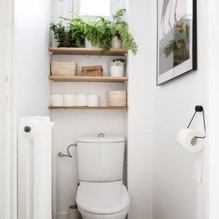 Пример оригинального дизайна: туалет среднего размера в современном стиле с унитазом-моноблоком, белыми стенами, полом из цементной плитки и разноцветным полом