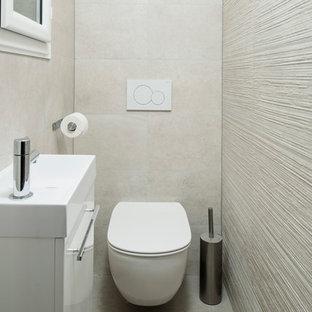 На фото: маленький туалет в современном стиле с инсталляцией, бежевой плиткой, керамической плиткой, бежевыми стенами, полом из керамической плитки, подвесной раковиной, плоскими фасадами, белыми фасадами и бежевым полом с