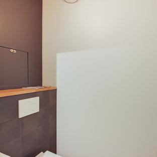 Стильный дизайн: маленький туалет в стиле модернизм с инсталляцией, черной плиткой, цементной плиткой, черными стенами, полом из цементной плитки, столешницей из дерева, черным полом и коричневой столешницей - последний тренд