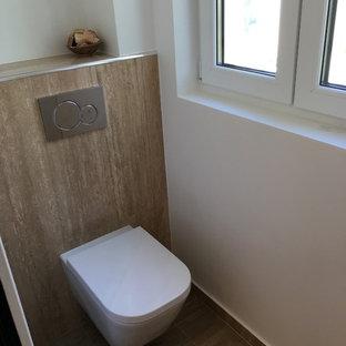 Идея дизайна: маленький туалет в стиле модернизм с инсталляцией, бежевой плиткой, белыми стенами, каменной плиткой и полом из травертина