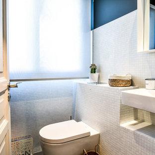 Exemple d'un WC et toilettes tendance avec un WC suspendu, un carrelage blanc, carrelage en mosaïque, un mur bleu et un lavabo suspendu.