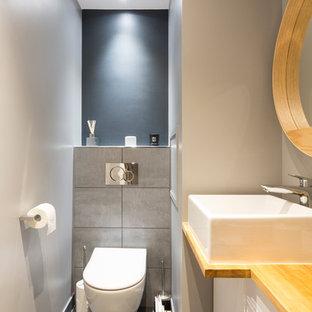 Cette photo montre un grand WC et toilettes scandinave avec un placard à porte plane, des portes de placard blanches, un WC suspendu, un carrelage gris, un mur gris, une vasque, un plan de toilette en bois, un sol gris, un plan de toilette marron, des carreaux de porcelaine et un sol en carrelage de porcelaine.