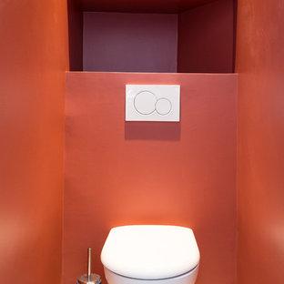 ロンドンの小さい北欧スタイルのおしゃれなトイレ・洗面所 (壁掛け式トイレ、フラットパネル扉のキャビネット、赤いキャビネット、赤い壁、テラゾーの床、白い床、白い洗面カウンター) の写真