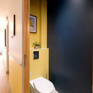 Idéer för att renovera ett funkis toalett, med en vägghängd toalettstol, gula väggar, cementgolv och gult golv