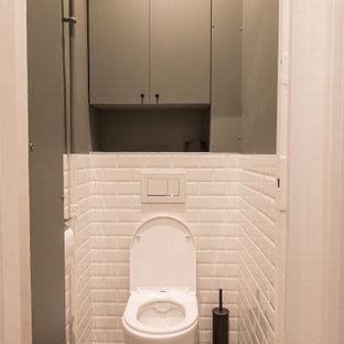 Пример оригинального дизайна: туалет в современном стиле с фасадами с декоративным кантом, зелеными фасадами, инсталляцией, белой плиткой, керамической плиткой, зелеными стенами, полом из цементной плитки, черным полом и встроенной тумбой