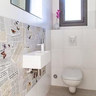 Réalisation d'un WC et toilettes design de taille moyenne avec un bidet, un carrelage blanc, des carreaux de céramique, un mur beige, un sol en carreaux de ciment, une grande vasque, un plan de toilette en surface solide et un sol beige.