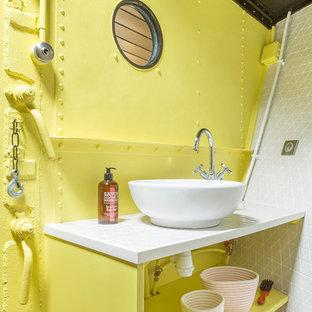 パリのビーチスタイルのおしゃれなトイレ・洗面所 (オープンシェルフ、黄色いキャビネット、黄色い壁、ベッセル式洗面器) の写真